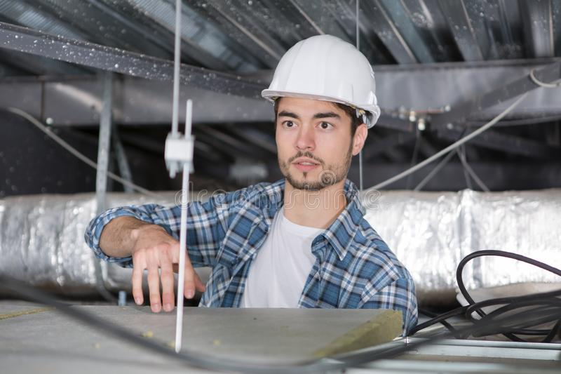 Male electrician on stepladder installing ceiling light stock images