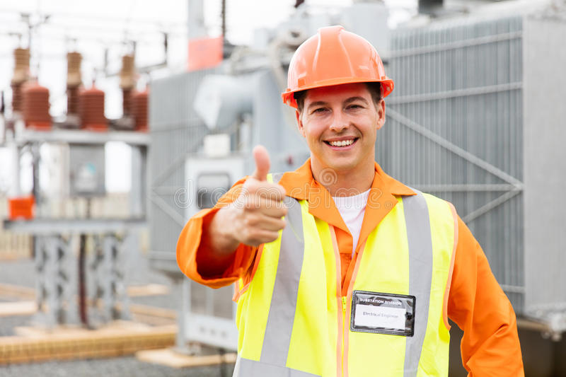 Male electrician thumb up. Happy male electrician with thumb up at electric substation stock photo