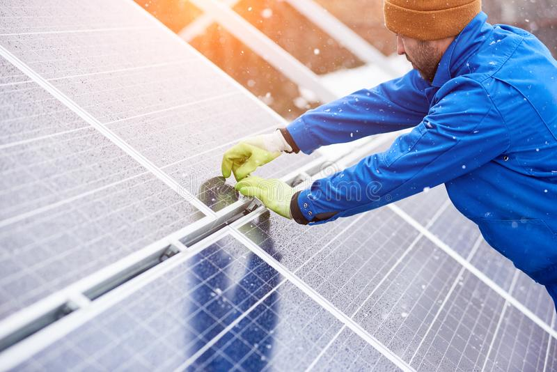 Professional electrician worker installing solar panels. Male electrician worker repairing solar panels outdoors alternative energy source environment friendly royalty free stock photo