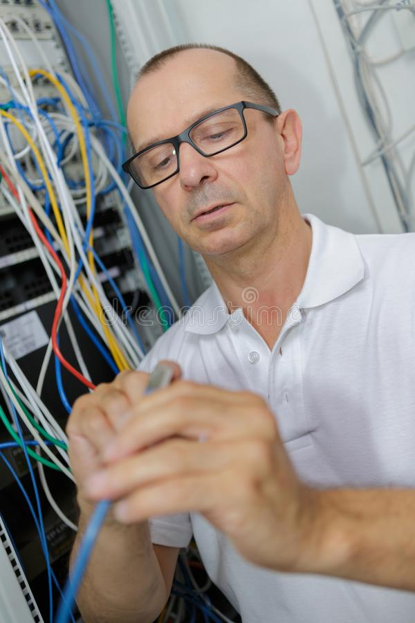 Male electrician working on fusebox stock images