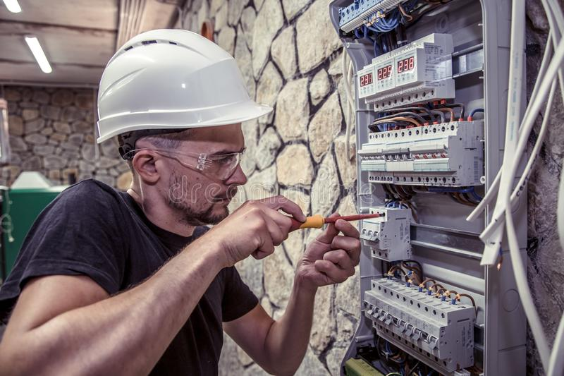 A male electrician works in a switchboard with an electrical con royalty free stock photos