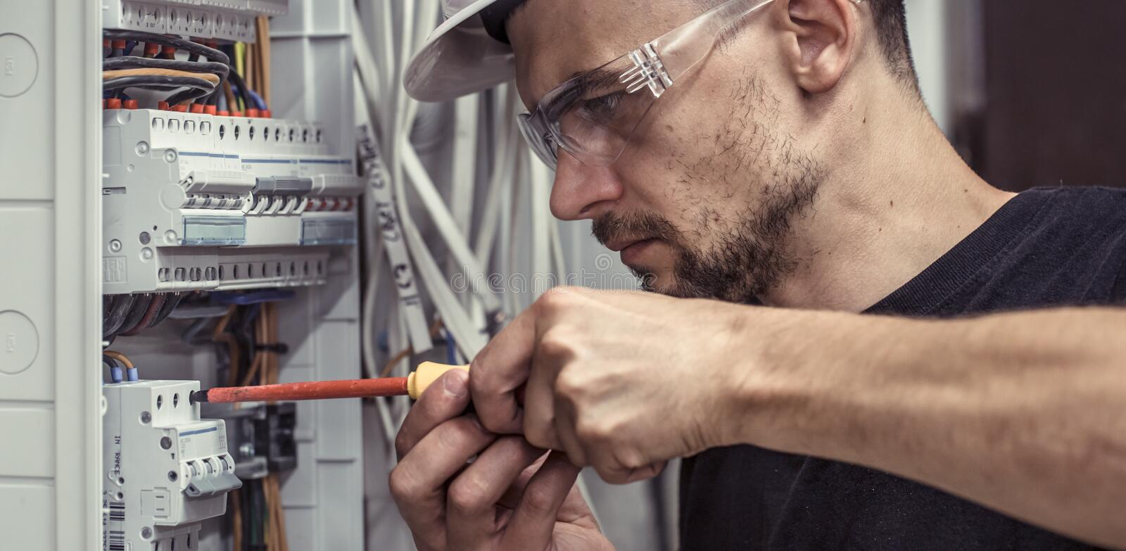 A male electrician works in a switchboard with an electrical con stock image