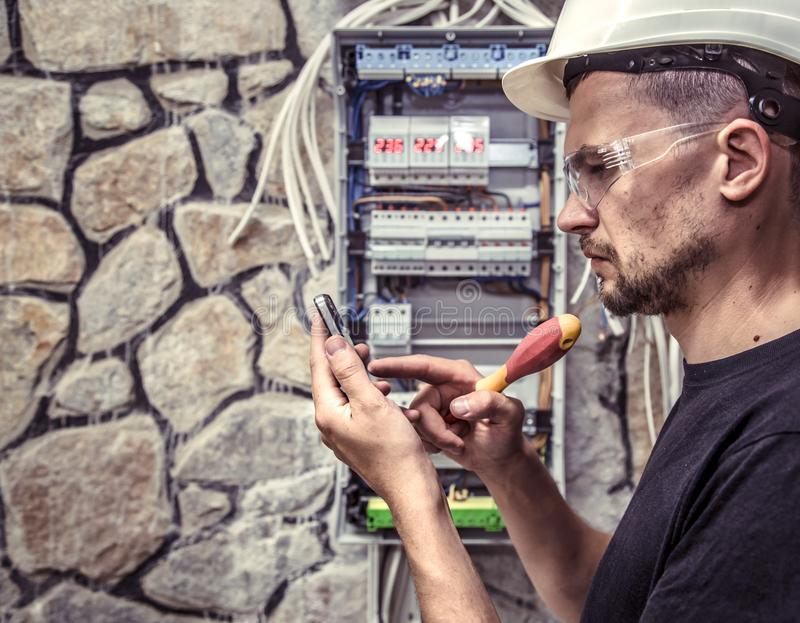 A male electrician works in a switchboard with an electrical con stock photos