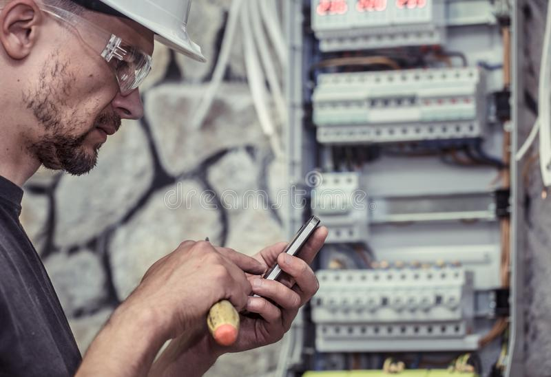 A male electrician works in a switchboard with an electrical con royalty free stock photography