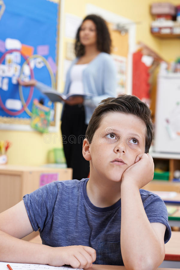 Male Elementary School Pupil Daydreaming In Class Stock ...
