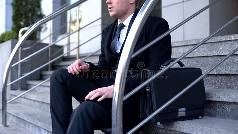 Male employee sitting on office building stairs, work problem, bankruptcy. Stock photo stock photos