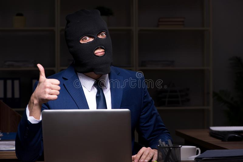 Male employee stealing information in the office night time royalty free stock images