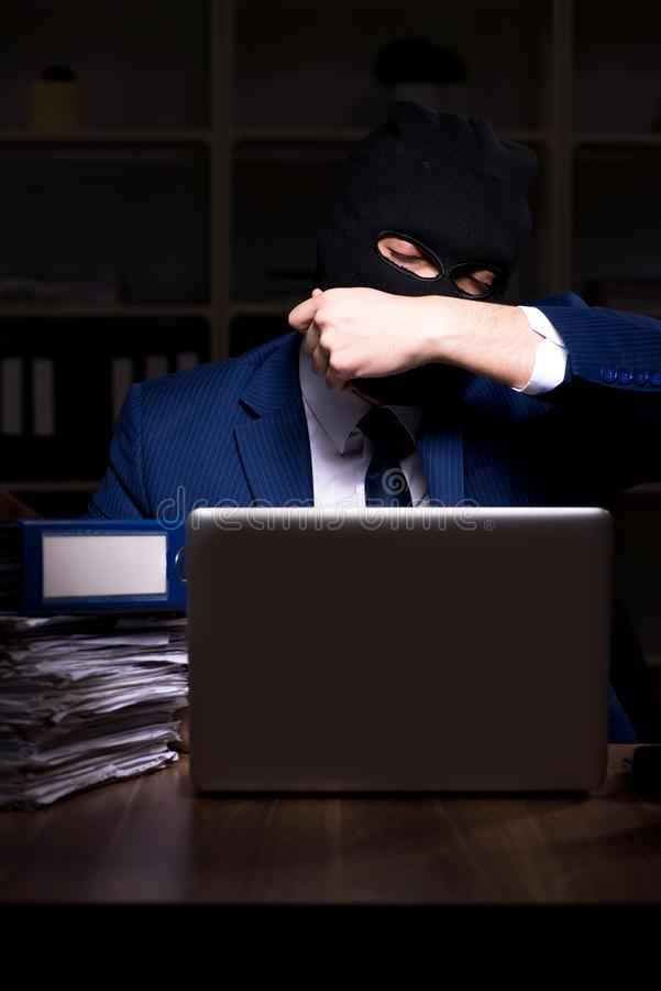 Male employee stealing information in the office night time royalty free stock photos