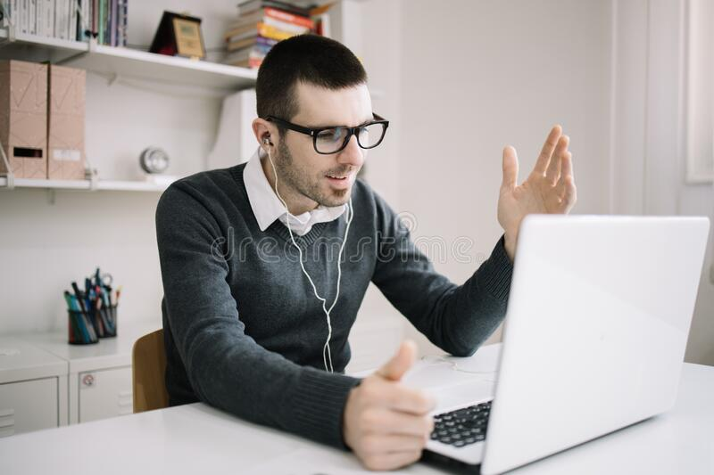 Male employee takes part in online meeting. Bearded businessman with headphones having an online conference meeting stock photo