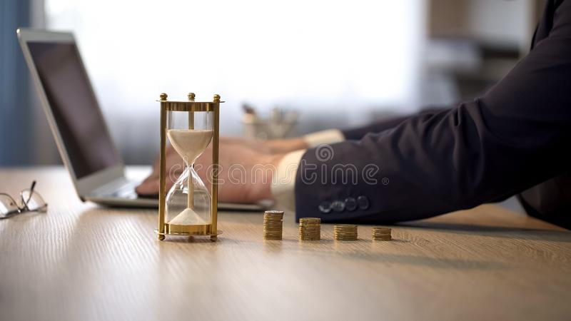 Male employee working on laptop, hourglass standing on desk, money investment stock photos