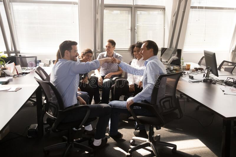 Male employees give fists bump engaged in office training stock photo