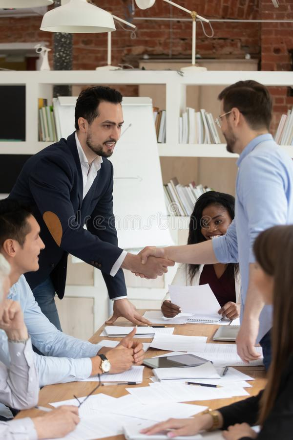 Male employees handshake get acquainted at business meeting. Smiling male colleagues shake hand congratulate with business success or promotion, happy diverse royalty free stock photos