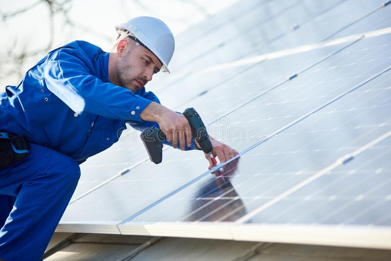 Electrician mounting solar panel on roof of modern house stock photography