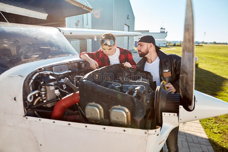 Male engineer and his son looking at plane engine compartment, check up before flight royalty free stock image