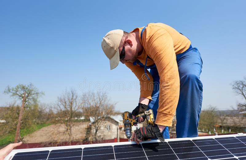 Electrician mounting solar panel on roof of modern house royalty free stock photo