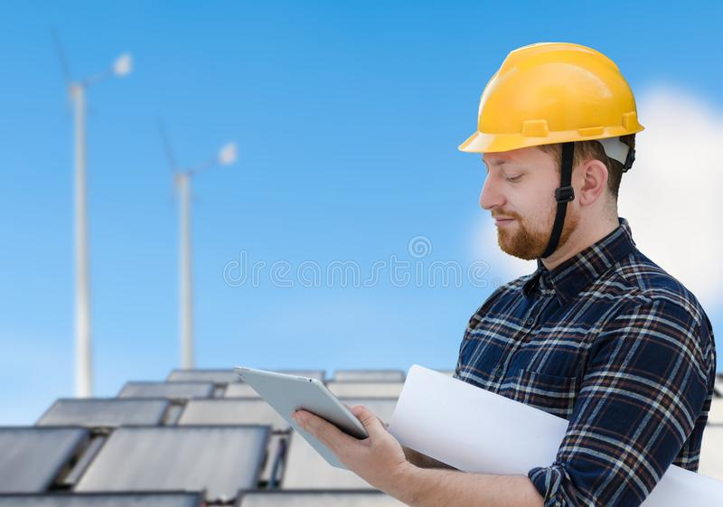 Male engineer at solar cell site with a tablet royalty free stock images