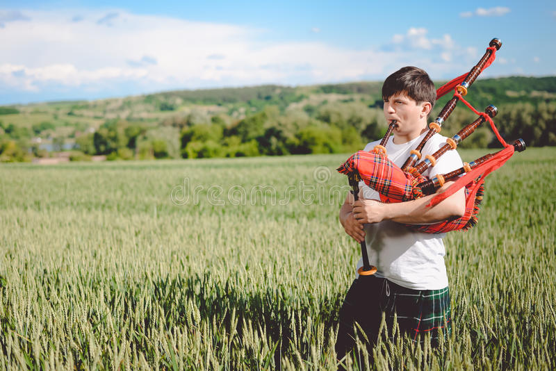 Male enjoying playing pipes in traditional kilt on green outdoors copy space summer field. stock photography