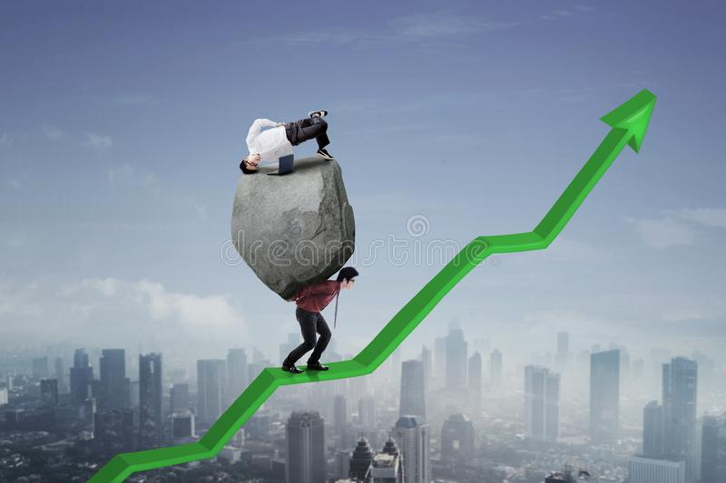 Male entrepreneur carrying his partner on an arrow. Male entrepreneur carrying a stone and his partner with laptop while climbing on an upward arrow royalty free stock images