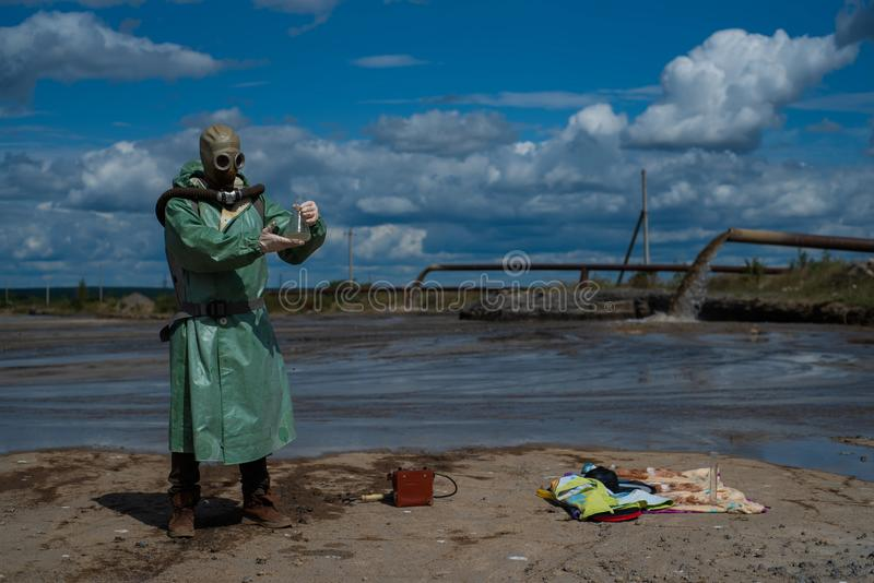 A male environmentalist in a green protective suit and gas mask takes a sample of water in a polluted lake for research. Waste production. Scientist doing stock photo