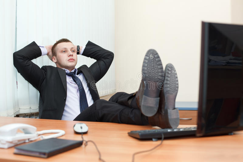 Male esting with feet on desk stock images