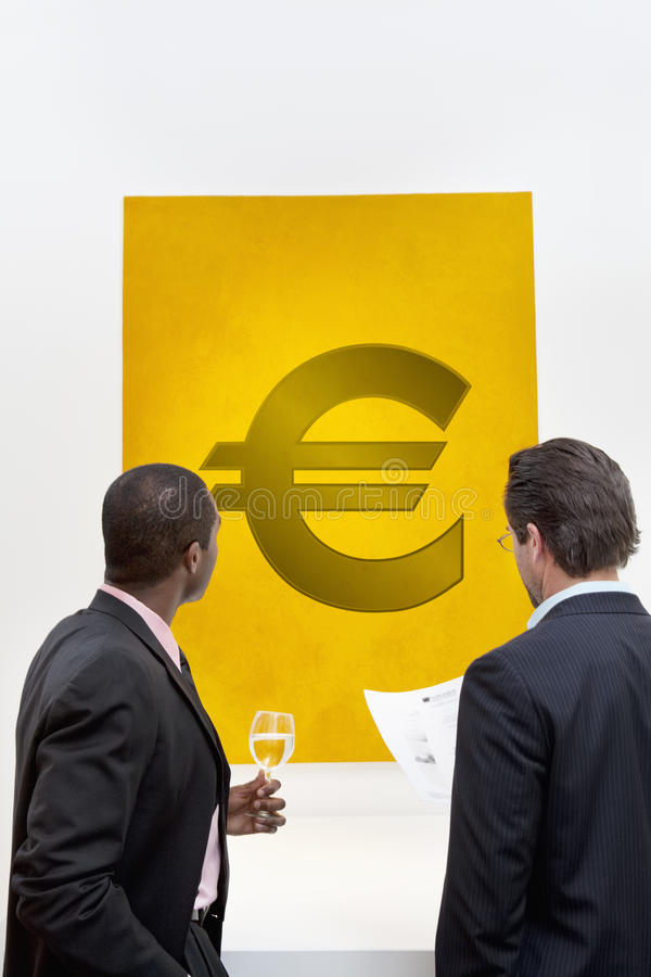 Download Male Executive Looking At Euro Sign Over White Background Stock Photo - Image: 30851436