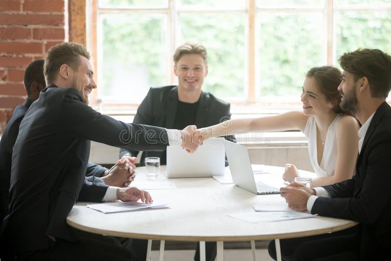 Male executive shaking hands with female coworker, teamwork intr royalty free stock photos