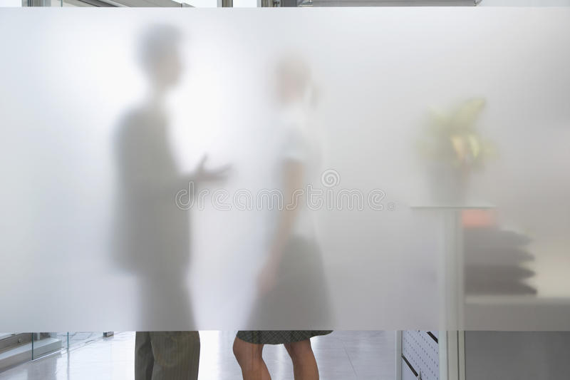 Male Executive Talking To Female Colleague Behind Translucent Wa. Side view of a male office worker talking to female colleague behind translucent wall in office royalty free stock images