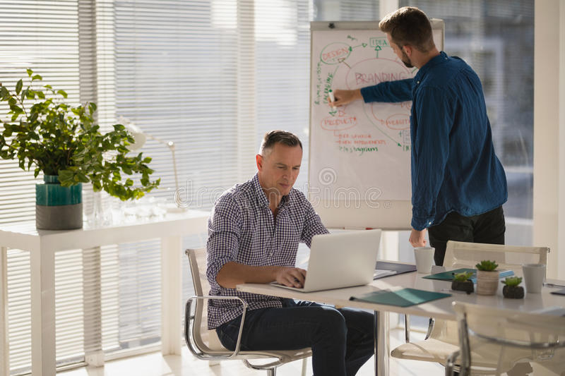 Male executive using laptop while coworker writing on flip chart. In the office stock photos