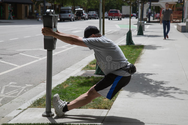 Male exercising stretching street park meter royalty free stock photo