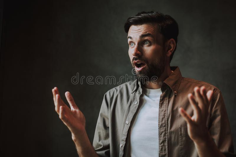 Male expressing astonishment and gesticulating hands indoor royalty free stock photography