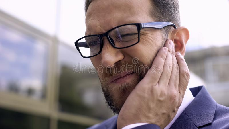 Male in eyeglasses has ear pain, bacterial infection, inflammation, otitis. Stock photo royalty free stock image