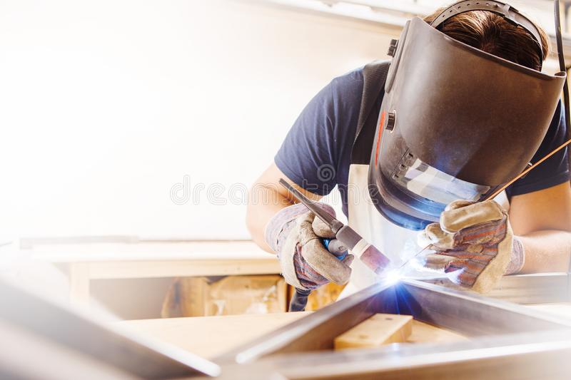 Male in face mask welds with argon-arc welding. Male in face mask, protective gloves welds with argon-arc welding. Welder makes weld seam on metal frame. Worker royalty free stock photos