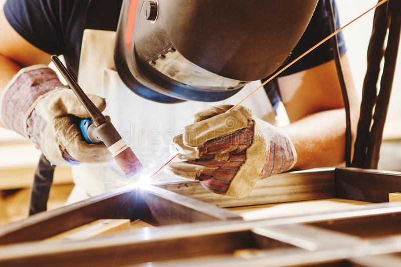 Male in face mask welds with argon-arc welding. Male in face mask, protective gloves welds with argon-arc welding. Welder makes weld seam on metal frame. Worker stock image