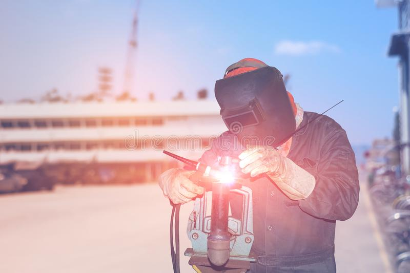 Welding factory. Male in face mask welding with argon and arc welding in factory on Monochrome background royalty free stock photo