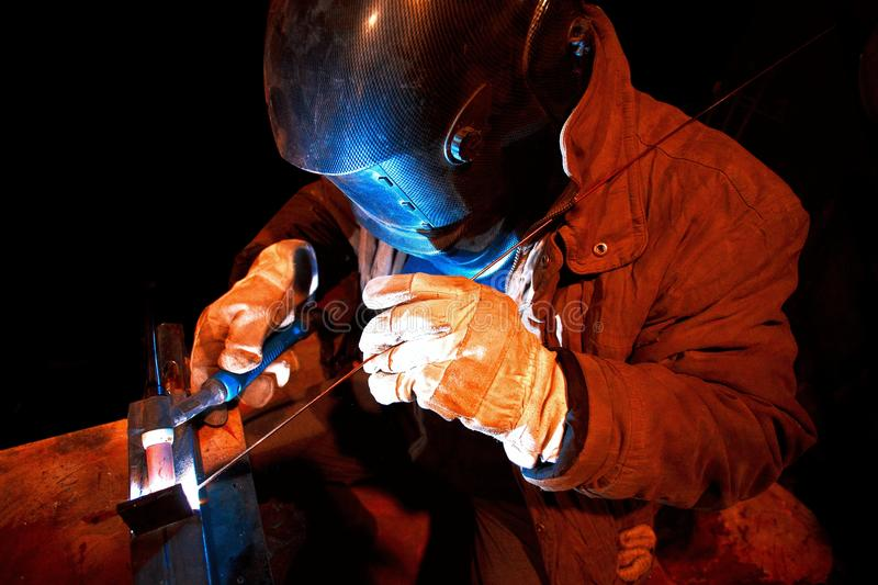 Male in face mask welds with argon-arc. Welding stock photography