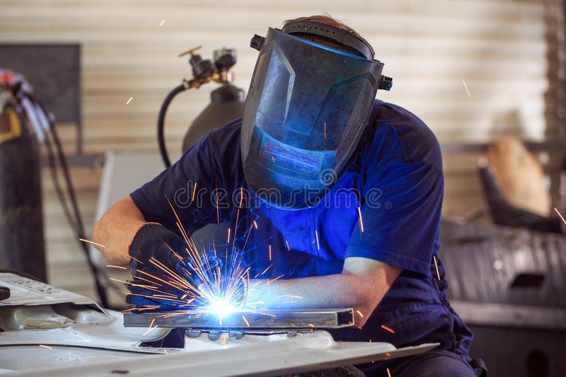 Male in face mask welds with argon-arc welding. In body shop stock photo