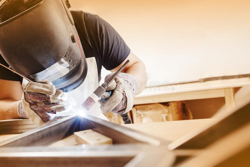 Male in face mask welds with argon-arc welding. Male in face mask, protective gloves welds with argon-arc welding. Welder makes weld seam on metal frame. Worker stock images
