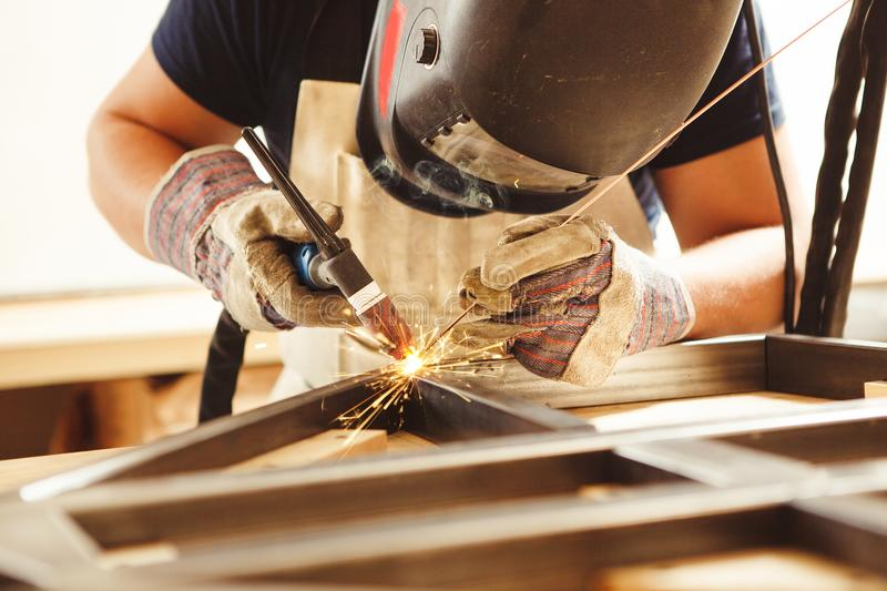 Male in face mask welds with argon-arc welding. Male in face mask, protective gloves welds with argon-arc welding. Welder makes weld seam on metal frame. Worker stock photo
