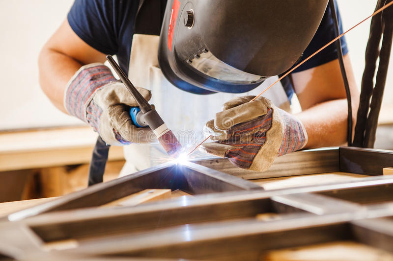 Male in face mask welds with argon-arc welding. Male in face mask, protective gloves welds with argon-arc welding. Welder makes weld seam on metal frame. Worker stock photography