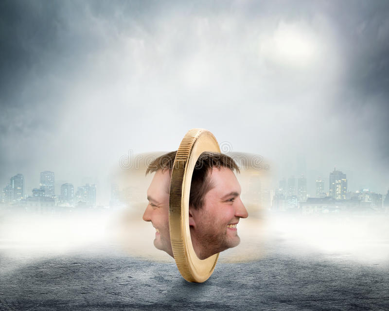 Male face on two sides of the coin. Is spinning over grey foggy background royalty free stock photos