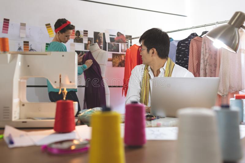 Male fashion designer talking with female designer while working on laptop stock photo