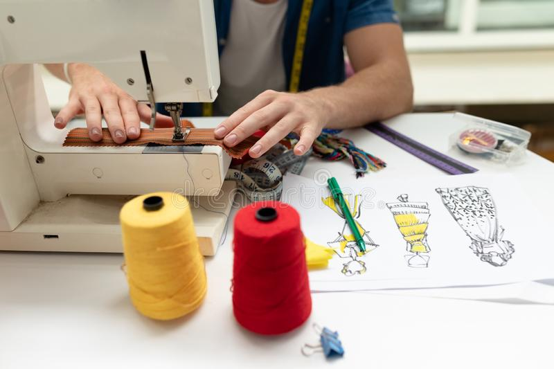 Male fashion designer using sewing machine on a table in design studio. Mid section of Caucasian male fashion designer using sewing machine on a table in design royalty free stock images