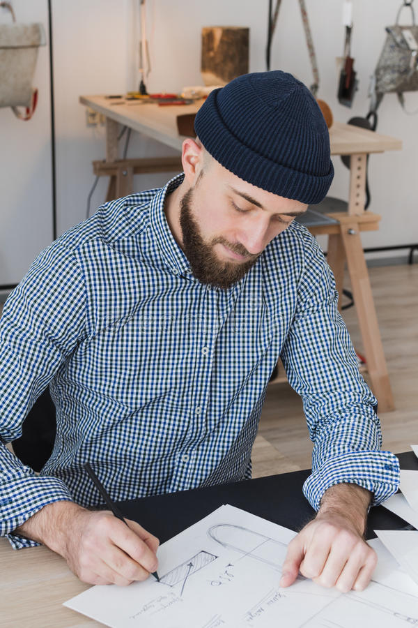 Male fashion designer working on a concept of a new product. In his small workshop royalty free stock images