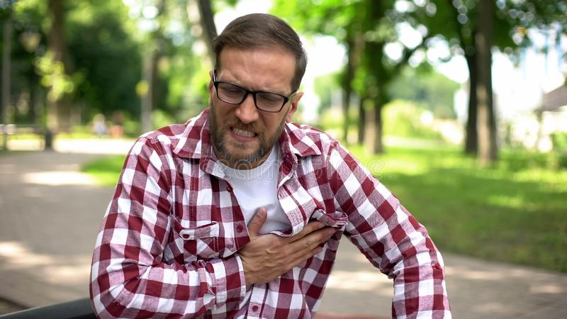 Male feeling chest pain, sitting outdoors, heart arrhythmia, ischemic disease stock image