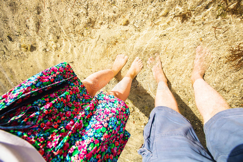 Male and feemale legs standing in shallow water. Male and female legs standing in shallow water on the sand seen from above. Selfie, point of view stock photo