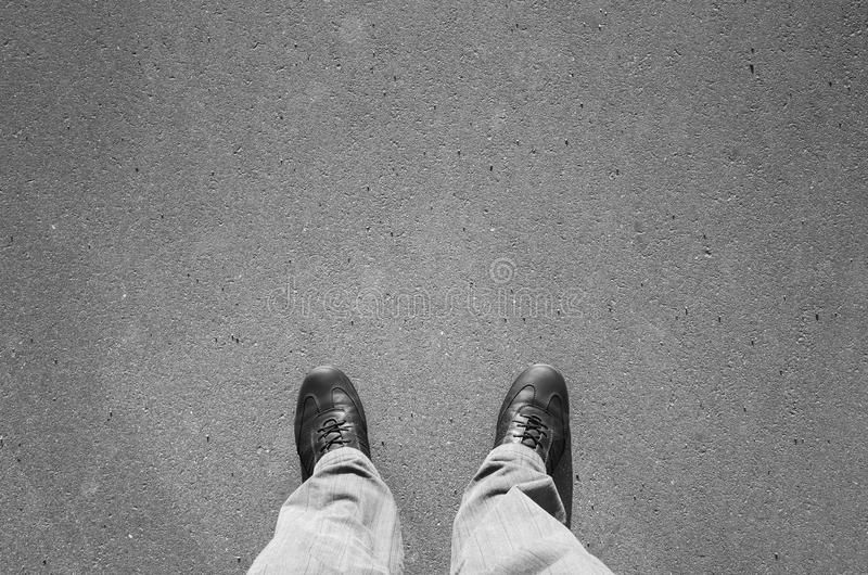 Male feet in black new shining leather shoes. Standing on urban asphalt pavement stock photos