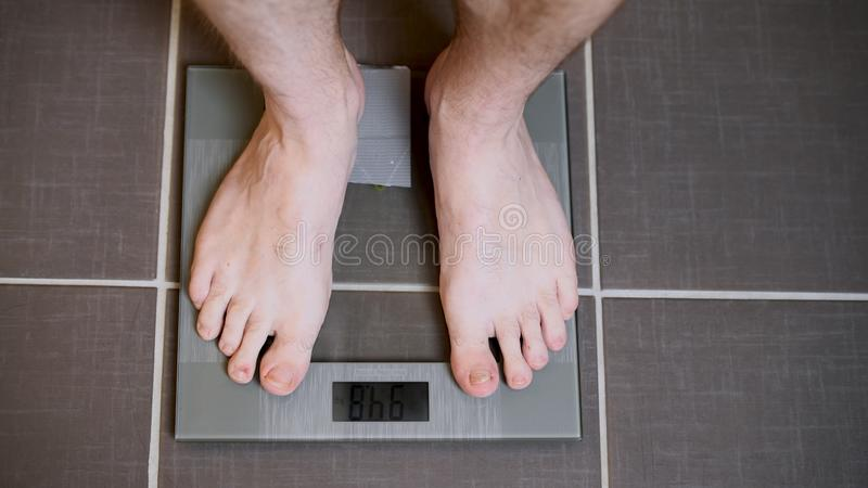 Male feet on glass scales, men`s diet, body weight royalty free stock photography