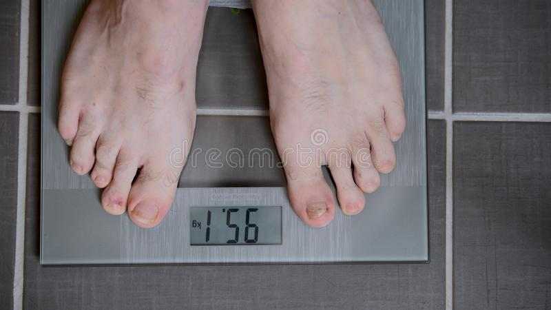 Male feet on glass scales, men`s diet, body weight stock photography