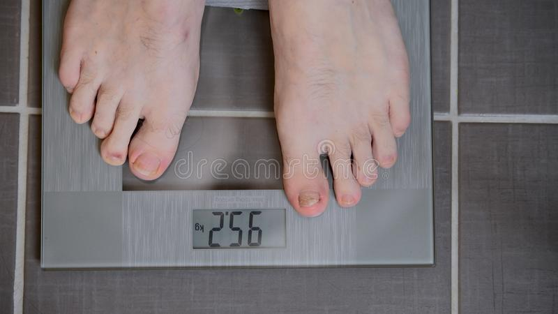 Male feet on glass scales, men`s diet, body weight stock image