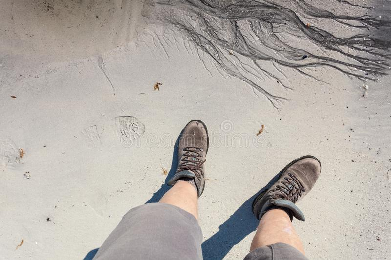 Male feet in hiking shoes on beach. Male feet in hiking shoes on sandy beach. Summertime royalty free stock images